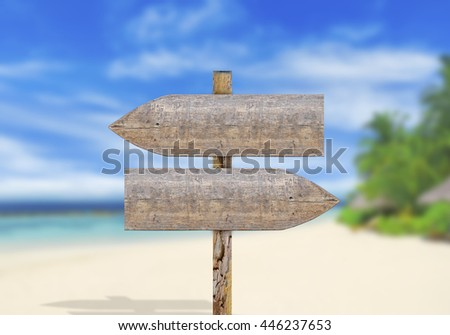 Wooden direction sign on beach - stock photo