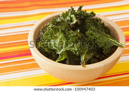 Wooden dish of roasted kale chips on a colorful table cloth - stock photo