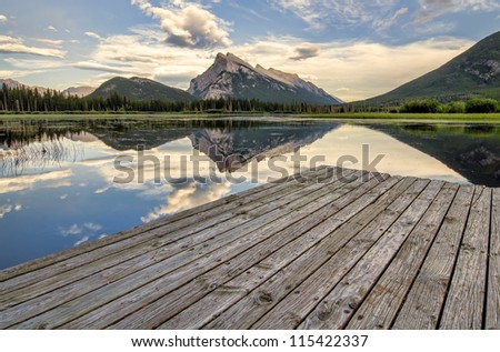 Wooden dock beside Vermilion lakes with perfect mountain reflection. - stock photo