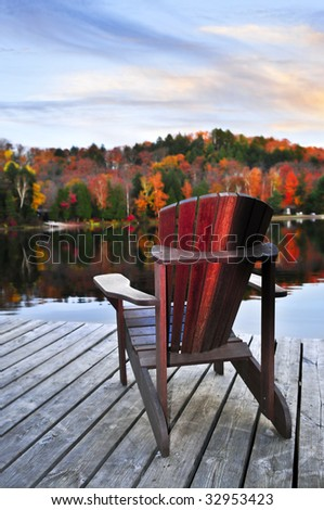 Wooden dock with chair on calm fall lake - stock photo