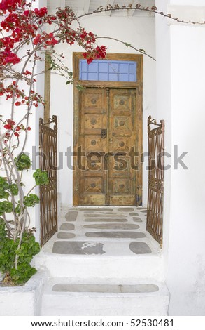 Wooden door and an old iron gate with blooming bougainvilleas - stock photo