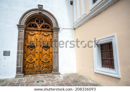 Wooden door and window of the Sagrario church in Quito, Ecuador - stock photo