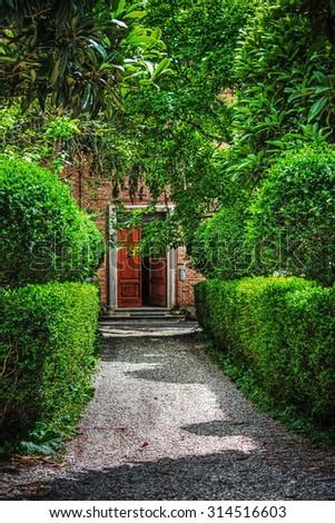 wooden door in a beautiful italian garden - stock photo