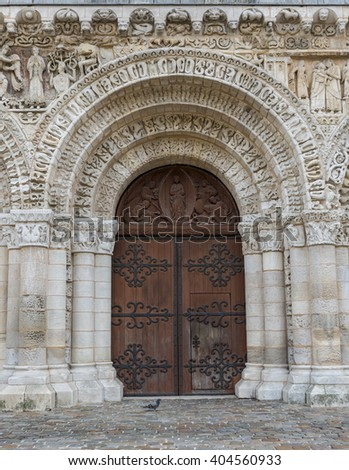 Wooden door of the church of Poitiers in France. - stock photo
