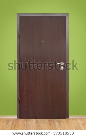 Wooden door on green wall background - stock photo