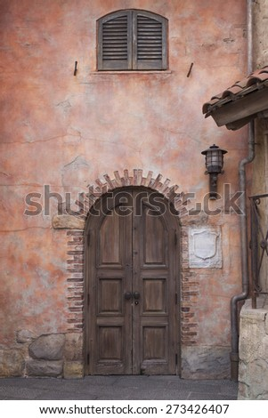 wooden door on old Italian styled brick wall with lamp and window - stock photo
