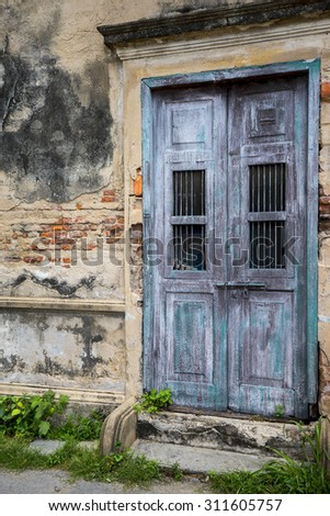 Wooden door on old wall at abandoned facade. - stock photo