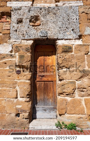 Wooden Door - San Gimignano Tuscany Italy / Detail with wooden door, entrance to the medieval tower in San Gimignano town (UNESCO heritage), Siena, Tuscany, Italy - stock photo