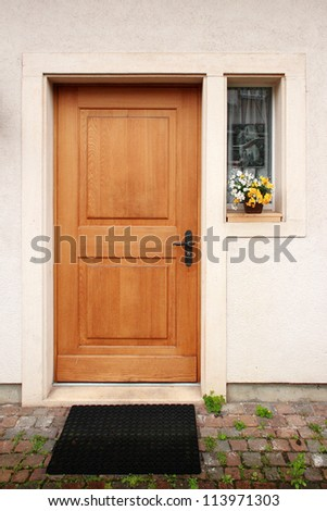 Wooden door, small window on the side, flower in pot on the window sill - stock photo
