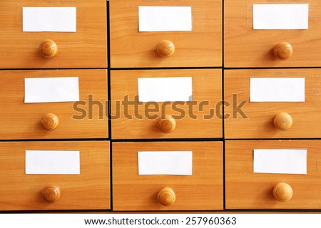Wooden drawers with catalog cards in library, closeup - stock photo