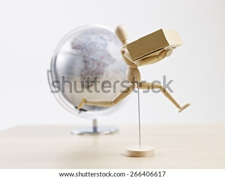 wooden dummy carrying cardboard box with globe in the background, global logistics concept. - stock photo