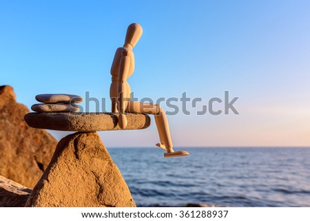 Wooden dummy in balance on the edge stone  - stock photo