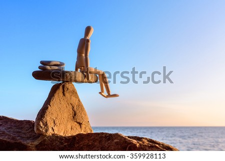 Wooden dummy in balance on the top of stone  - stock photo