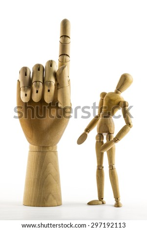 Wooden dummy looks at big hand with raised finger - stock photo