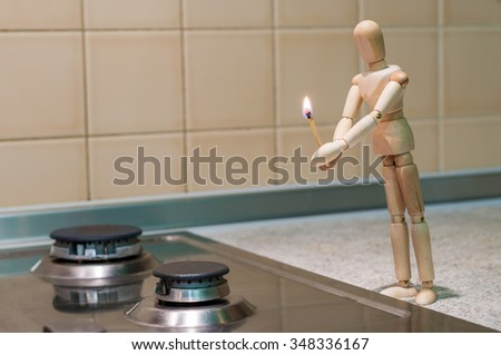 Wooden dummy, mannequin or man figurine holding a burning match and tryi to light or ignite a gas stove. No gas because of debts for utilities. - stock photo