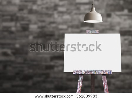 Wooden easel with blank painting canvas in the room - stock photo