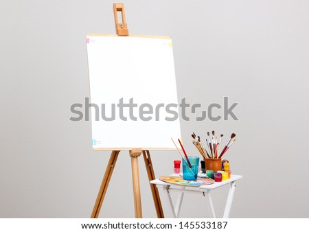 Wooden easel with clean paper and art supplies in room - stock photo