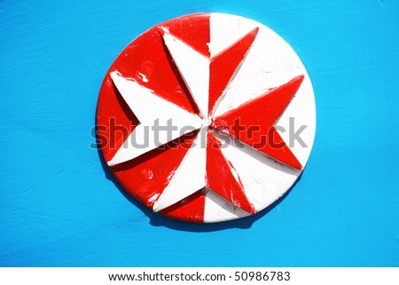 wooden eight pointed cross painted in white and red on a bright blue background - stock photo