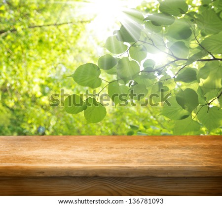 Wooden empty table with green leafs for Your product display - stock photo