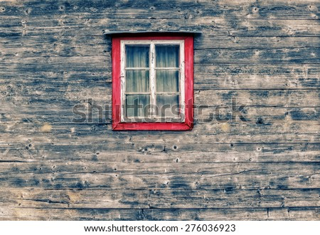 Wooden facade of a mountain hut with an old window with bleached red frame and curtains  in the center of the picture. - stock photo