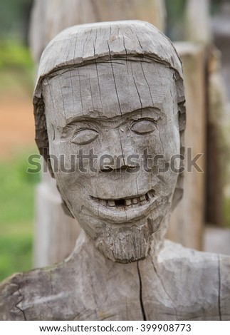 Wooden face smiling, close up. Statue of human character of minority group. - stock photo