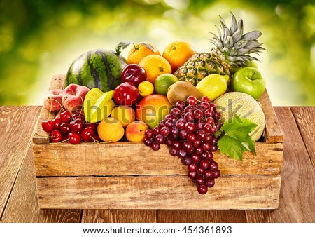 Wooden farm crate filled with fresh tropical fruit on an outdoor table at market including with bananas, watermelon, grapes, orange, lemon, kiwi, peaches, apricot, cherry, pineapple, melon and apples - stock photo