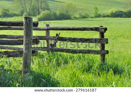 wooden fence in a meadow green grass - stock photo
