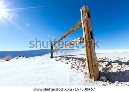 wooden fence in snowy wilderness and sun - stock photo