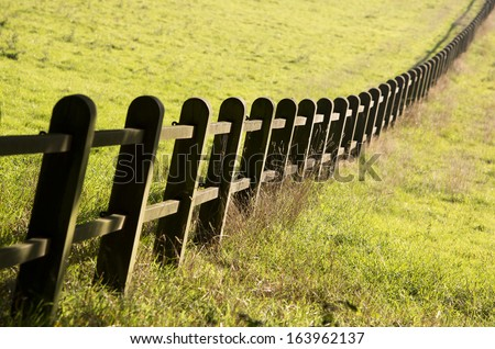 Wooden fence in the grasslands - stock photo