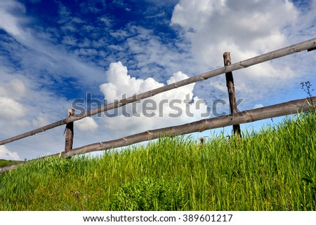 wooden fence on grassland with blue sky - stock photo