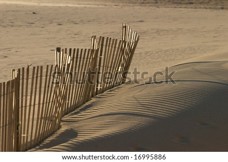 wooden fence waving along the beach sand - stock photo
