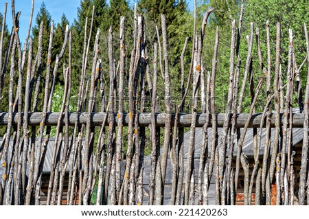 Wooden fence woven out of thin rods - stock photo
