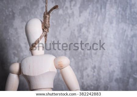 Wooden figure of human hanging in the hangmans loop - stock photo