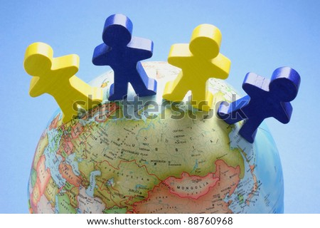 Wooden Figures on Globe with Blue Background - stock photo