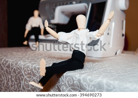 wooden figurine of a man in a white shirt near the sewing machine. - stock photo