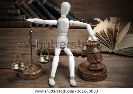 Wooden Figurine With Judges Gavel And Scale Of Justice And Old Law Book On The Rough Wood Table Background - stock photo