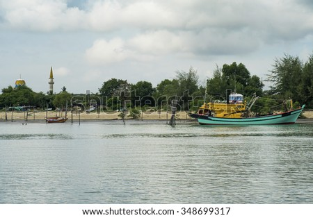 Wooden fisherman boat at a river with dramatic sky during sunny day - stock photo