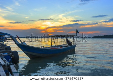 Wooden fisherman boat with sunset background - stock photo