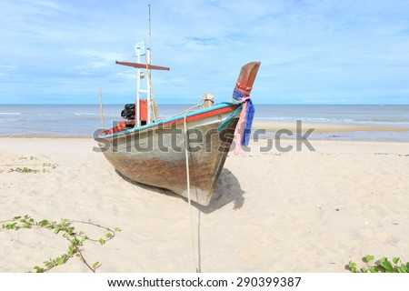 Wooden fishing boat on the beach with blue sky - stock photo