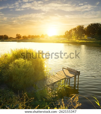 Wooden fishing pier by the river at sunrise - stock photo