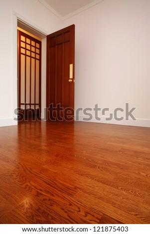 Wooden floor and entrance door in empty room - stock photo