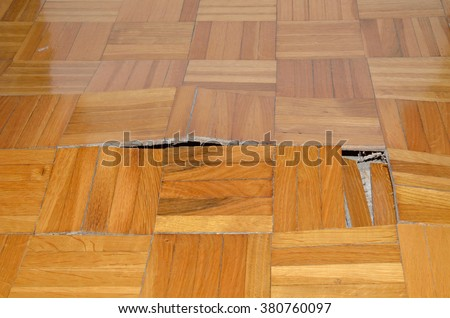Wooden floor in apartment with floor damaged by destructive elements such as wet, moisture, water. - stock photo