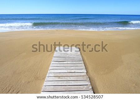 Wooden floor on golden sandy beach - stock photo