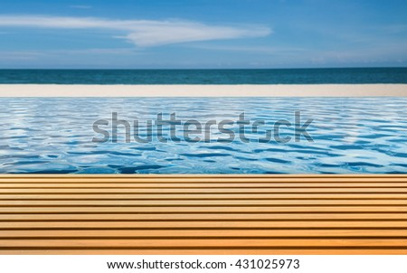 wooden floor with 3d rendering infinity pool on beach background - stock photo