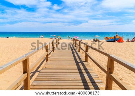 Wooden footbridge to sandy beach in Armacao de Pera coastal town, Algarve region, Portugal - stock photo