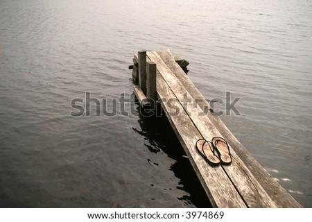 wooden footbridge with pair of oriental flip-flops - stock photo