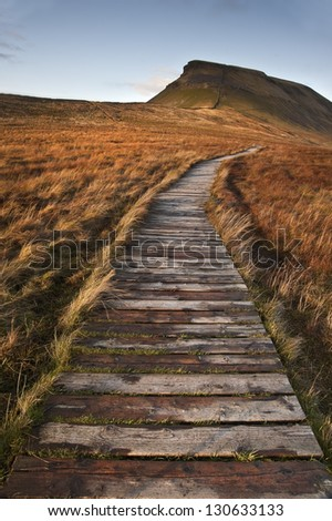 Wooden footpath over marshland leading to Pen-y-Ghent in Yorkshire Dales National Park - stock photo