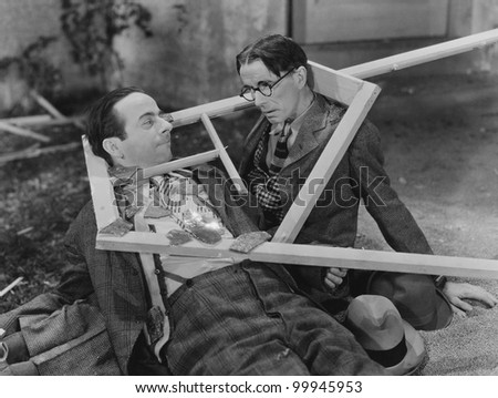 Wooden frame broken over two mens heads - stock photo