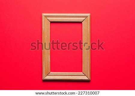 wooden frame on red background - stock photo