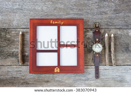Wooden frame on wooden background with colored pencils and retro clock. - stock photo
